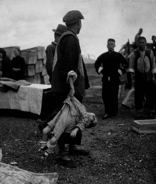 Body of Chinese child killed during Japanese attack is carried like a sack to a common grave; treatment due in no small part to the extremely high numbers of casualties among the Chinese civilian population at the hands of brutal Japanese soldiers. 1937