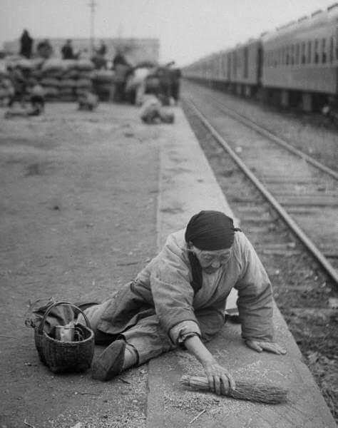 An aged refugee fighting hunger, sweeps up spilled rice on the railroad station platform. November 1949